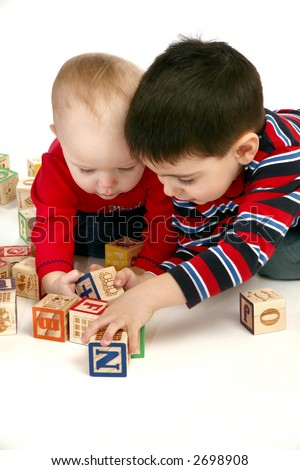 Brother and baby sister playing with blocks over white background. - stock photo