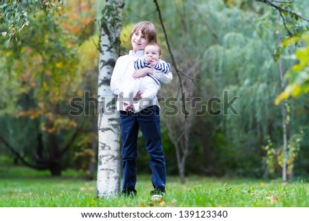 Brother and baby sister walking in a park - stock photo