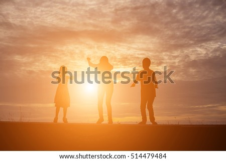Brother and brother silhouette,Moments of the child's joy. On the Nature sunset