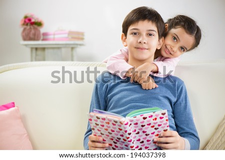 Brother and cute little sister reading book at home
