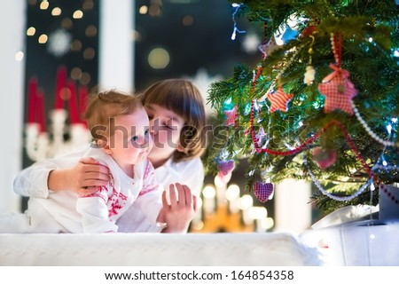 Brother and his baby sister playing together at a Christmas tree in a dark living room - stock photo