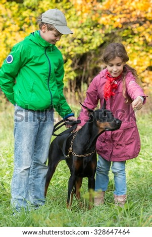 Brother and his sister are playing with the dobermann in the park. - stock photo