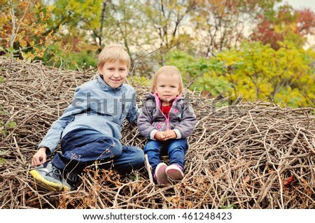 brother and little sister on the woods in fall