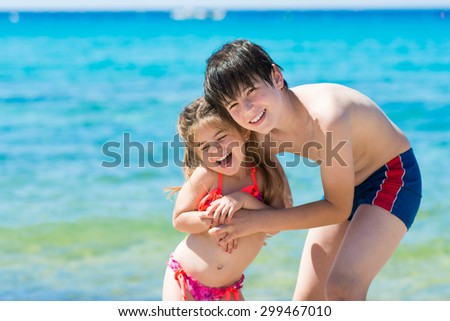 Brother and little sister playing at the beach, blue sea background - stock photo