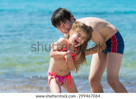 Brother and little sister playing at the beach, blue sea background