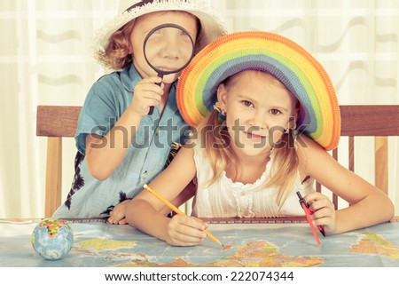 brother and sister are considering a world map with a magnifying glass - stock photo