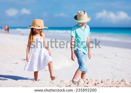 Brother and sister at beach enjoying vacation - stock photo