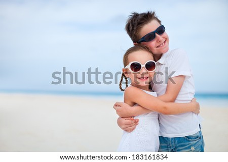 Brother and sister at beach hugging each other - stock photo