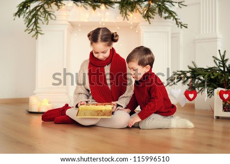brother and sister at Christmas. Happy children at the fireplace - stock photo