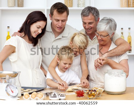 Brother and sister baking in the kitchen with their grandparents and parents