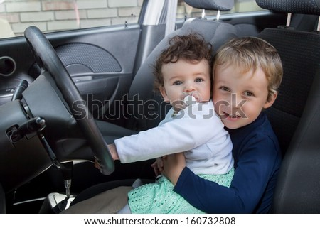 Brother and sister behind the wheel car - stock photo