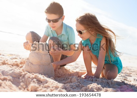 Brother and sister building sand castle at tropical beach - stock photo