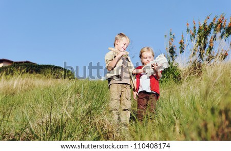Brother and sister children playing pretend adventure game outdoors having fun in the field - stock photo