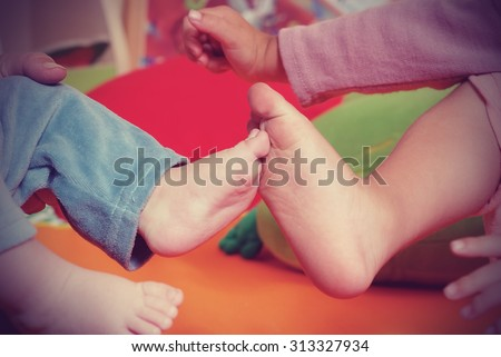 Brother and sister children's feet  in nursery - stock photo