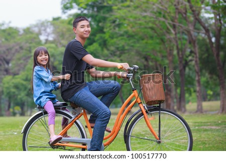 Brother and sister cycling bicycle at the park - stock photo