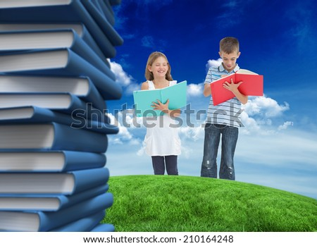 Brother and sister doing their homework together against green field under blue sky - stock photo