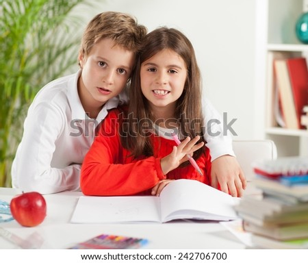 Brother and sister doing their homework together. Elementary age.