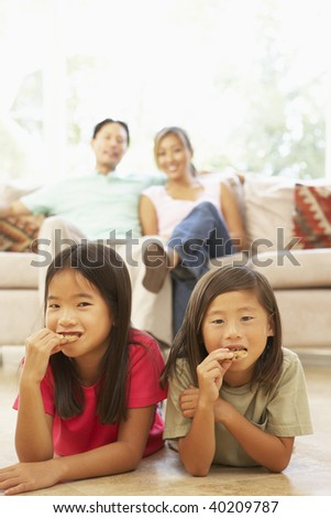 Brother and Sister Eating A Cookie At Home - stock photo
