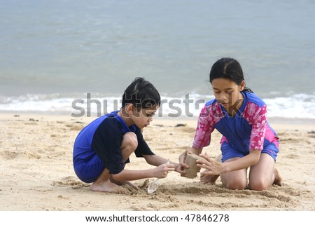 Brother and sister enjoying making sandcastle by a tropical beach - stock photo