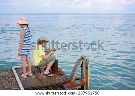 brother and sister go fishing on the docks - stock photo