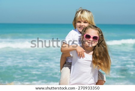 Brother and sister having fun at the beach - stock photo