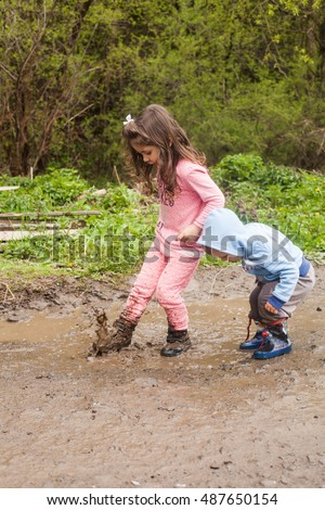 Brother and sister having fun splashing in a mud puddle