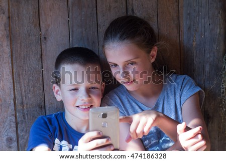 Brother and sister having fun with smart phone