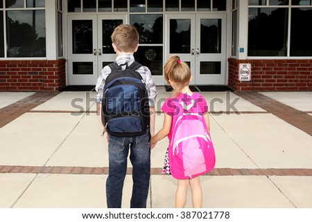 Brother and sister heading into school. - stock photo