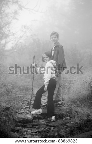 brother and sister hiking in foggy weather. - stock photo