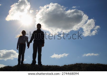 Brother and sister holding hands while standing on a hill against the sky - stock photo