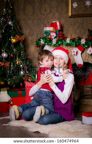 Brother and sister hugging near a Christmas tree - stock photo