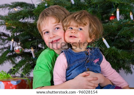 brother and sister in front of christmas tree