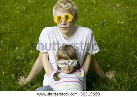 brother and sister in strange sunglasses sitting on grass in park - stock photo