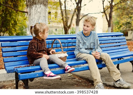 brother and sister in the park on the bench - stock photo