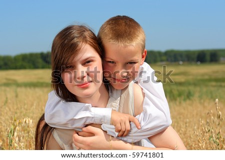 brother and sister in the summer field - stock photo
