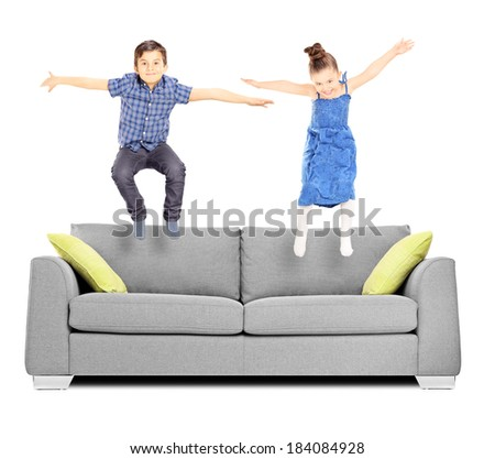 Brother and sister jumping on sofa isolated on white background - stock photo