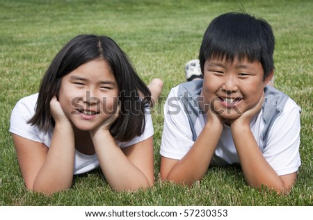 Brother and sister laying in the grass - stock photo
