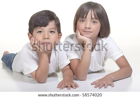Brother and sister laying on the floor in this studio image. - stock photo