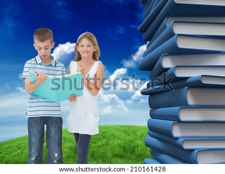 Brother and sister learning their lesson together against green field under blue sky - stock photo