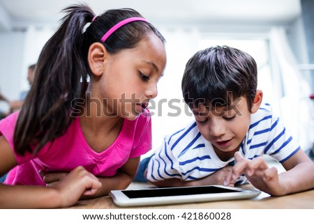 Brother and sister lying on floor and using digital tablet in living room - stock photo