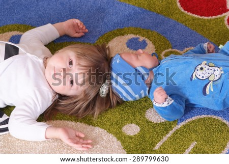 Brother and sister lying on the carpet - stock photo