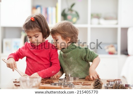 Brother and sister making cookies in a kitchen