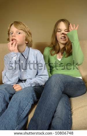 Brother and sister making faces while getting family portraits done. - stock photo