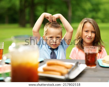 brother and sister making fun a cookout picnic - stock photo