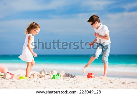 Brother and sister making sand castle at tropical beach - stock photo