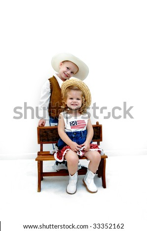 Brother and sister model cowgirl and cowboy outfits.  They are both smiling and wearing hats and boots. - stock photo