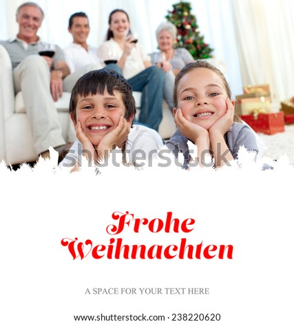 Brother and sister on floor with their family in Christmas against christmas greeting in german - stock photo