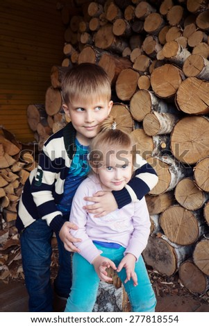 brother and sister on the background of wood logs