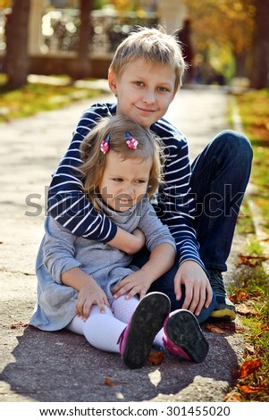 brother and sister outdoors in fall time - stock photo