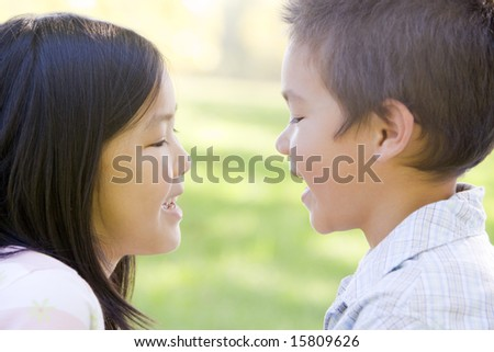 Brother and sister outdoors staring at each other and smiling - stock photo